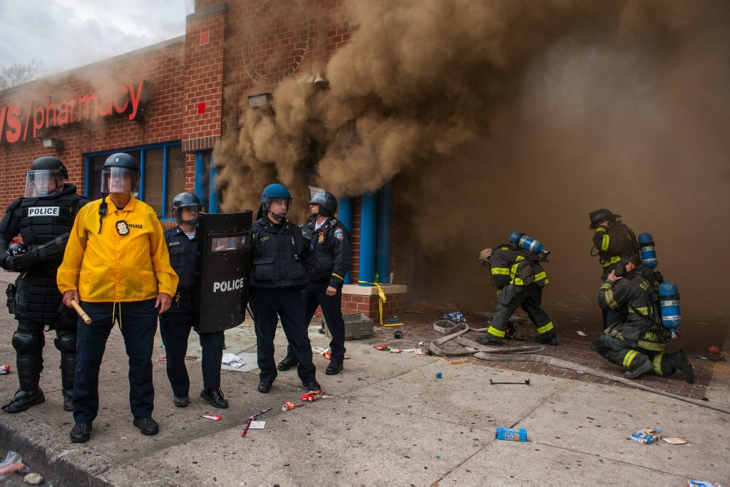 epaselect epa04723489 Police stand by a CVS that was on fire as firefighters arrive to fight the blaze, during a protest for the death of Freddie Gray in Baltimore, Maryland, USA, 27 April 2015. Gray died of spinal cord injuries on 19 April while in police custody; the US Justice Department announced that they are launching their own investigation into the case. EPA/NOAH SCIALOM