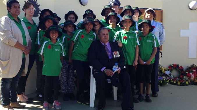 HONOURING SOLDIERS: Cherbourg Junior Police Rangers gather around Vietnam veteran Eric Law at the new Boys From Barambah War Memorial.
