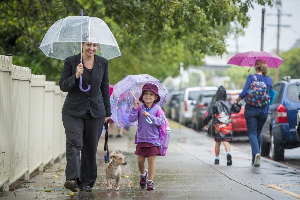 Sarah and her daughter Hollie, 5, with Bindi the dog, make the trek home after a rainy day in Gladstone.