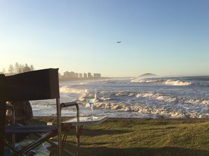 People watch on as the sun sets over big swell at Alexandra Headland.