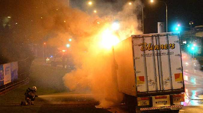 MYSTERY BLAZE: Gympie Fire and Emergency Service officers battle to extinguish a truck fire on the Bruce Hwy on Friday night.
