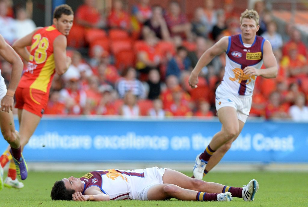 Tom Rockliff of the Lions is knocked out after colliding with Steven May of the Suns during the round five AFL match between the Gold Coast Suns and the Brisbane Lions at Metricon Stadium on May 2, 2015 in Gold Coast, Australia.