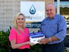 Unitywater Health and Well-being Co-ordinator Debbie Miller takes delivery of Bowel Scan kits from Noosa Rotary Club Treasurer Frank O'Dea