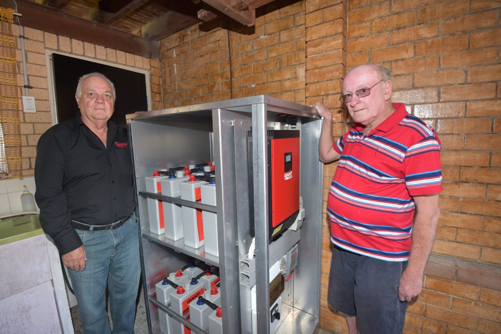 State sales manager for Giant Power, Peter West, left, with Buddina homeowner Don Scobie and his new off-grid hybrid power system with battery back-up.