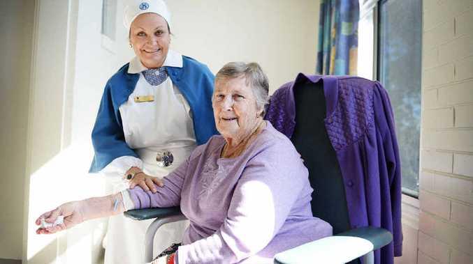 NURSING FLASHBACK: Jenni Prosser, surgical ward nurse unit manager, and patient Marie Mackney, at St Vincent's Hospital in Lismore. Ms Prosser is wearing a 1950s nursing uniform to celebrate International Nurses Day.