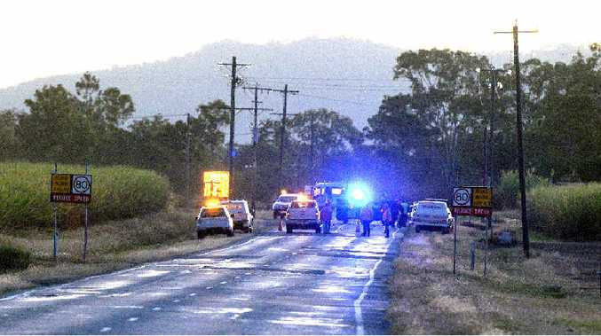 Police at the scene of a fatal crash on Mackay-Eungella Road involving a car and a motorbike.