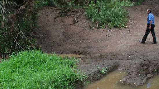 MUD BATH: Arthur Gorrie inspects the mess left by 4WD enthusiasts.