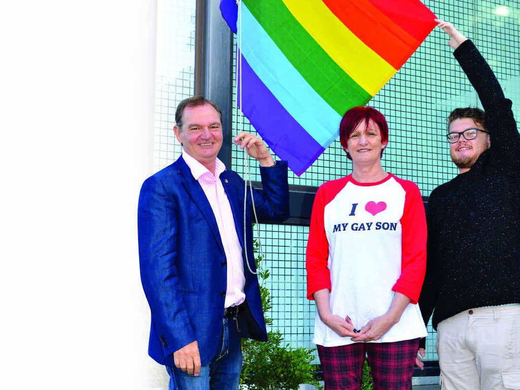 PROUD MOMENT: Mayor Paul Pisasale joins PFLAG members Deb Grading and Matthew Wells to raise the flag.