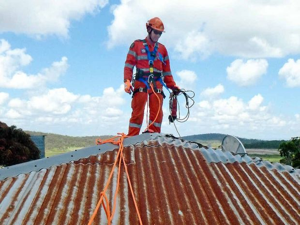 REPAIRS: Roof damage to homes was a big issue following Cyclone Marcia, with many insurance claims for it. Pictured is SES volunteer Ed Barrett securing a damaged roof.