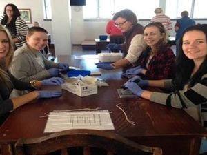 Students among volunteers assembling birth kits
