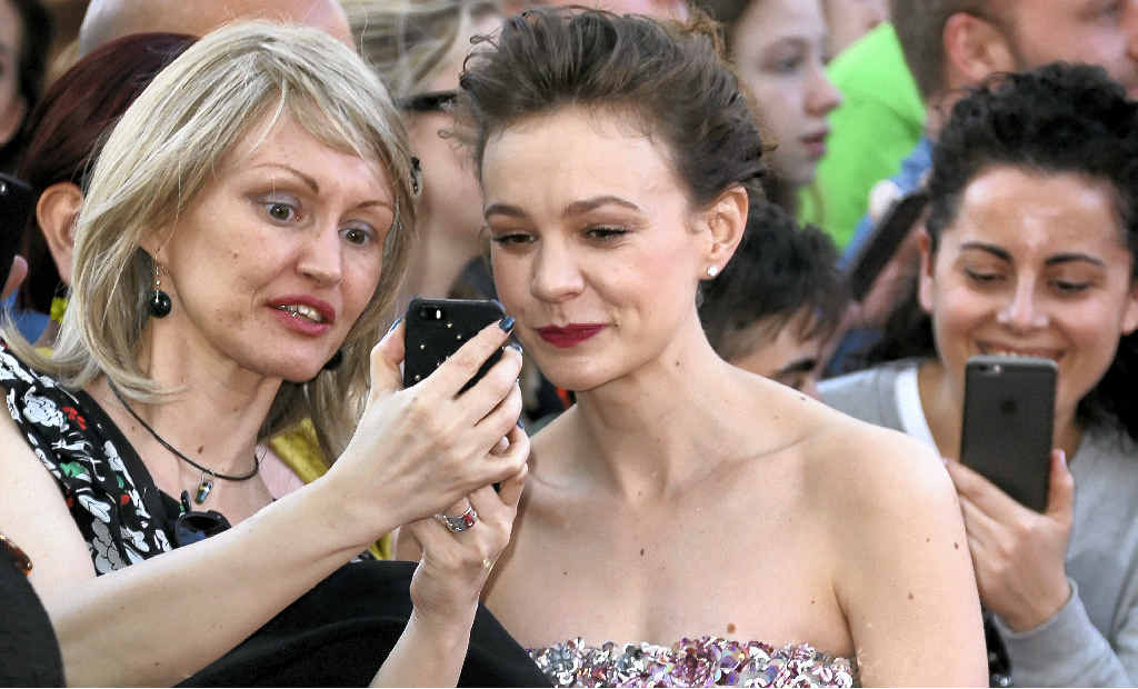 ABOVE LEFT: Carey Mulligan has a picture taken with a fan at the the world premiere of the film Far From The Madding Crowd in London. ABOVE RIGHT: Walking the Dorset countryside.