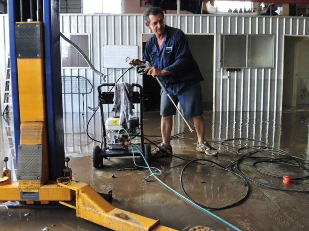 Gary Norman Duffy starts the clean up in his Keogh Street business after the 2013 flood. Photo: Rob Williams / The Queensland Times