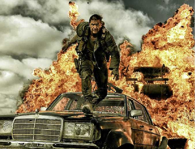 BLOW IT UP: Tom Hardy (Mad Max) strides over a Mercedes in an explosive scene from Mad Max: Fury Road.