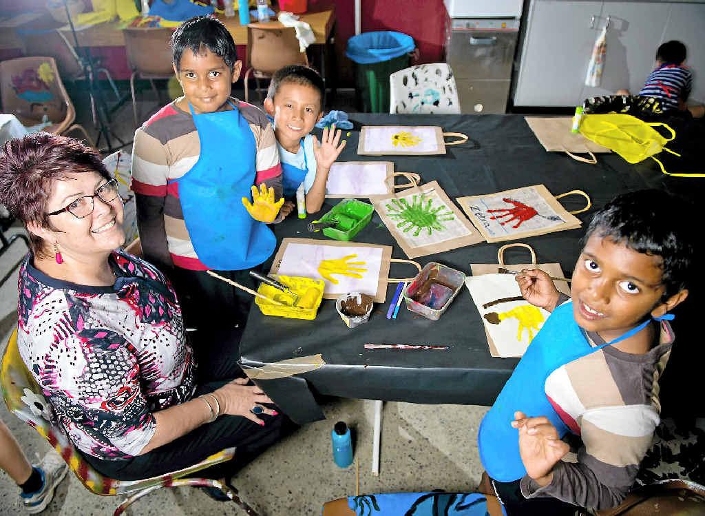 HANDS UP FOR FUN: Early Childhood Network's Lyn Hughes with Darren Fei, 7, Anupam Peetha, 7, and Nirupam Peetha, 7.