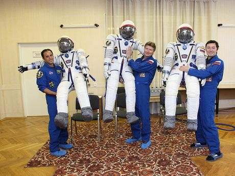 Astronauts in their flight suits, standing with their space suits. Astronauts are expected to swim laps of a pool wearing the blue flight suit and tennis shoes during early fitness training
