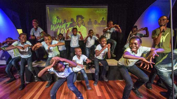 HIGH SPIRITS: Members of the Watoto choir from Uganda warm up for their Grafton performance at the community centre.
