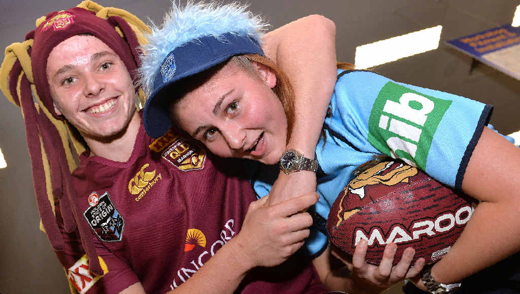Maroons fan Jake Christensen gets Blues supporter Beth Fuller in a headlock ahead of tomorrow's first State of Origin game. There's plenty of heated debate at Amart Sports Mackay where they both work.