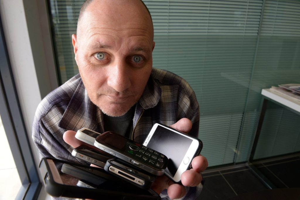 CALL ME: Scott Williams is fed up with the useless response he has been getting from Telstra. Having received several replacement phones, none of which worked, his patience has run out. Photo: Max Fleet / NewsMail