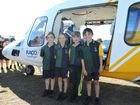Xavier College grade 2 students Layla Serdiule (L), Chloe Whitbread, Emma Garty and Cassidy Moore stand beside the RACQ Careflight helicopter.