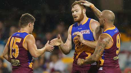BRISBANE, AUSTRALIA - AUGUST 17: Daniel Merrett of the Lions celebrates a goal with team mates (L) Dayne Zorko and (R) Ashley McGrath during the round 21 AFL match between the Brisbane Lions and the Greater Western Sydney Giants at The Gabba on August 17, 2013 in Brisbane, Australia. (Photo by Chris Hyde/Getty Images)
