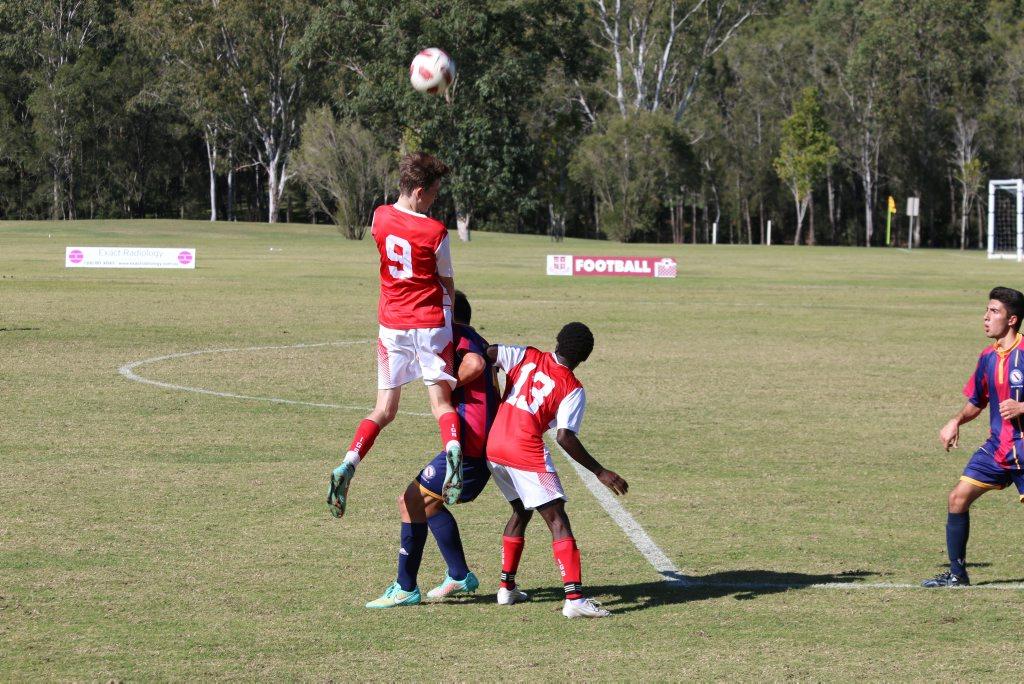 RISING FORTUNES: Ipswich Grammar School midfielder Oliver Bond flies high to win the header during the GPS football match with Brisbane High.
