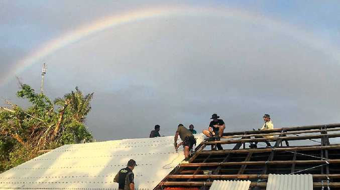 RAINBOW CONNECTION: The Evans Head team works on the roof of a Vanuatan church as a rainbow shines down.