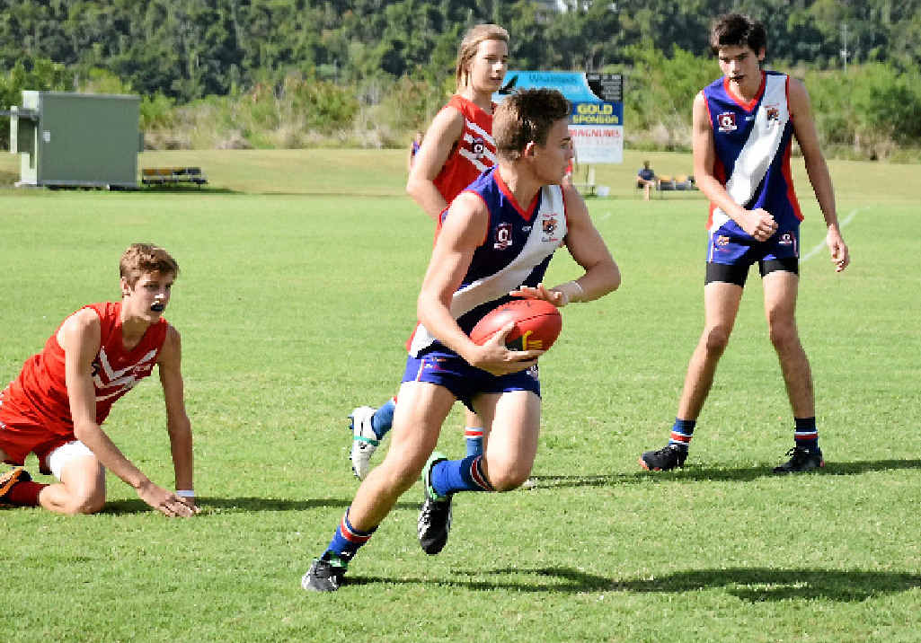 GAME ON: Sea Eagle Layton McGregor outruns Eastern Swans' players during Saturday afternoon's match. Photo Charlotte Lam / Whitsunday Times