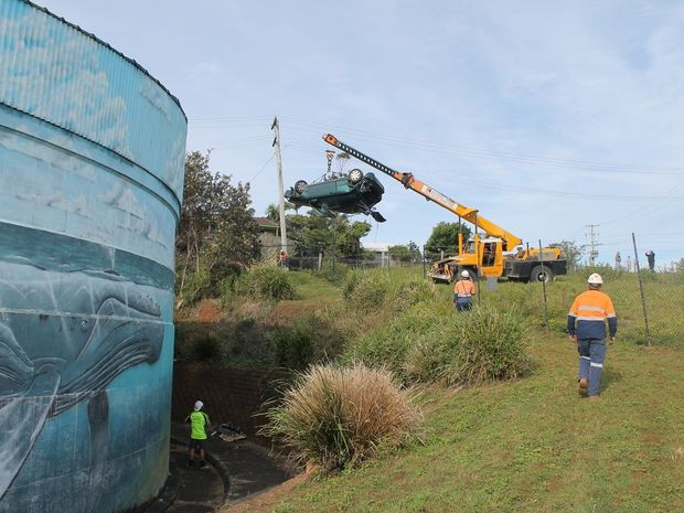 A crane is used on June 3 to retrieve a car that crashed through two fences and grazed a concrete wall before crashing onto the reservoir's access walkway at North Creek Road on May 23.