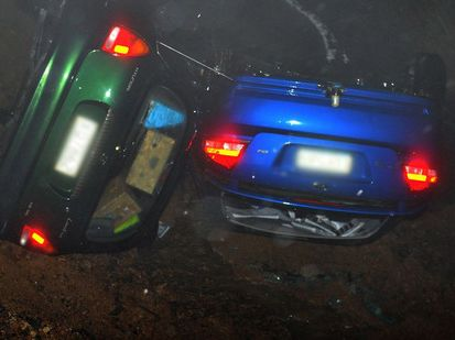 Two cars in a ditch after part of Highcliff Rd was swept away from in front of them last night.