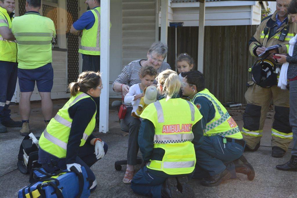 Queensland Ambulance paramedics talk to Gale Gray (sitting) holding grandaughter Jakayah Brown, 3, and (right) Kearhna Brown, 5. Photo Tara Miko / The Chronicle