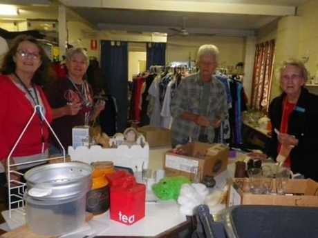 Blue Care volunteers sorting and pricing kitchen goods and toys.