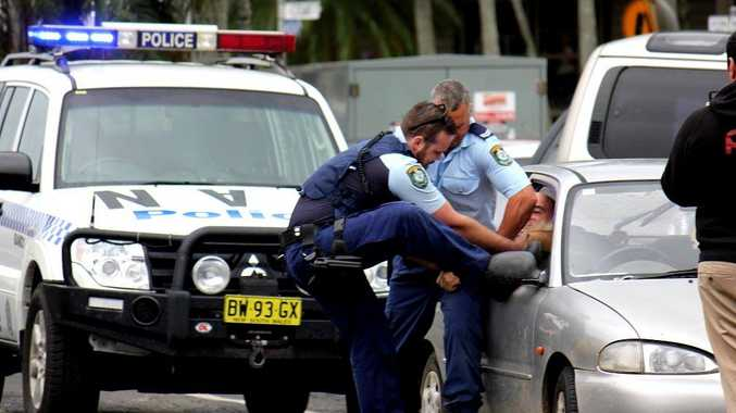 An image supplied by Trevor Avedissian showing police pulling a man through the smashed window of his car during an arrest at Mullumbimby.