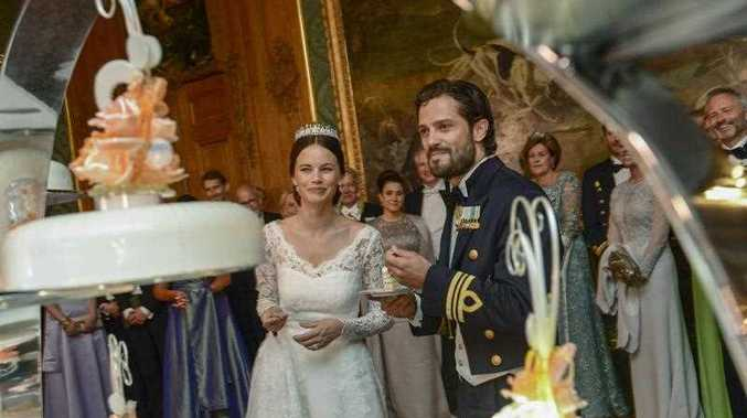Sweden's Prince Carl Philip, center right, and Sofia Hellqvist , center left, smile after cutting the wedding cake during their wedding in the royal place in Stockholm, Saturday, June 13, 2015