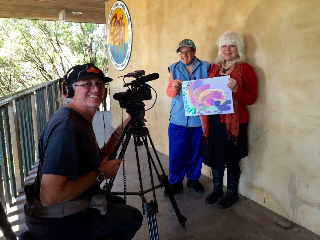 CREATEABILITY: Filmmaker Andy Bambach with artist Peta Krepski presenting one of her drawings to Karina Wynn-Moylan at Bay FM Photo