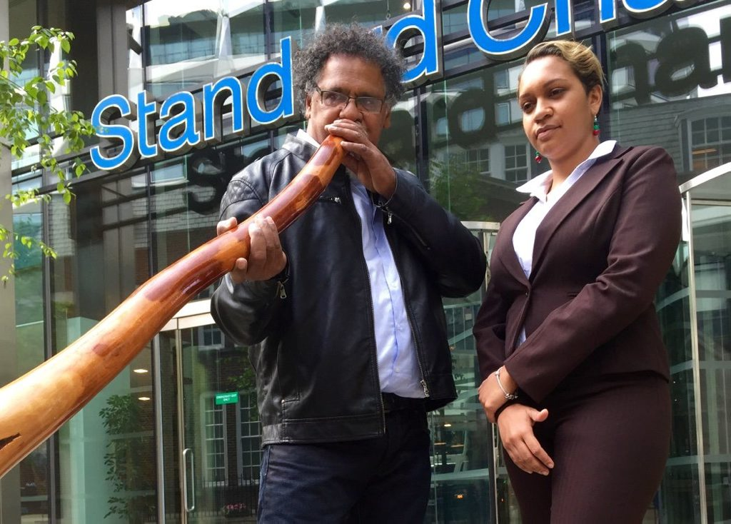 Murrawah Johnson and Adrian Burragubba outside Standard Chartered bank in London during their international trip urging the world's biggest banks not to fund Adani's Carmichael Mine project in the Galilee Basin.