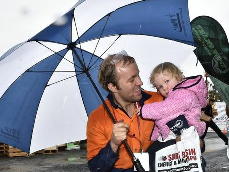 Braving the rain to llok at the displays at the Surat Basin Energy and Mining Expo at the Showgrounds are Brendan Winter and his daughter and Libby .