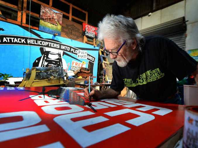 PEACE MESSAGE: Peace activist Graeme Dunstan puts the finishing touches to the mural which will be mounted on the side of the Peacebus to be used in anti-Talisman Sabre protests.