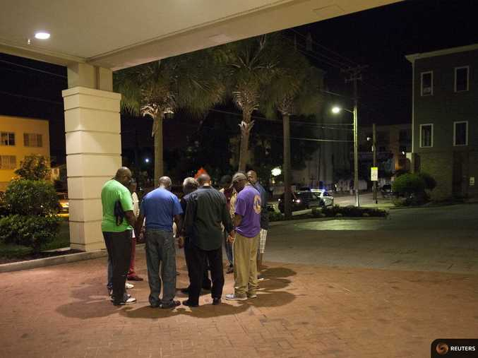 A small prayer circle forms nearby where police are responding to a shooting at the Emanuel AME Church in Charleston, South Carolina.