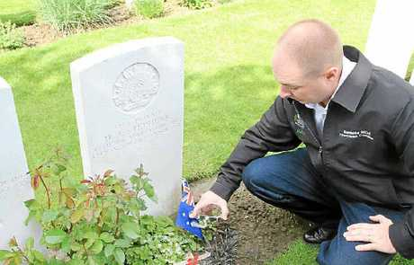 PAYING TRIBUTE: Brad Strong sprinkles soil from Bundamba Memorial Park on Ipswich soldier Private HJ Stephens' grave at Tyne Cot Cemetery.