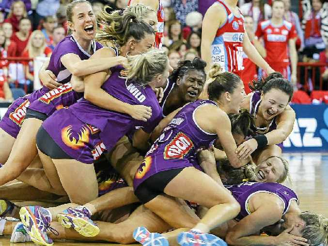 The Queensland Firebirds celebrate after winning the ANZ Championship.