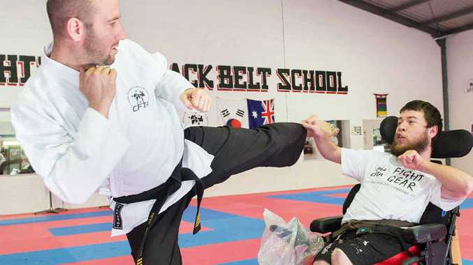 SMASHING BARRIERS: Luke Fieldhouse, who has cerebral palsy, with tae kwon do instructor Master Michael Landas. Trevor Veale
