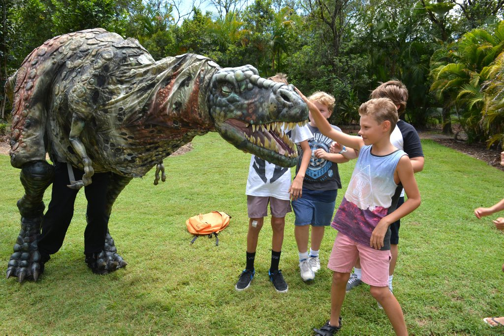 Lifesize dinosaur puppets at Australia Zoo for the holidays. Jed Bunter,10, from Mount Coolum makes a new friend at the Zoo. Photo: Warren Lynam / Sunshine Coast Daily