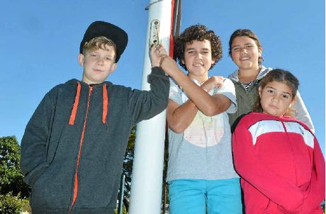 PROUD: Kaleb, Jiah, Lakkari and Moondara Mason raise the Aboriginal flag for NAIDOC Week.