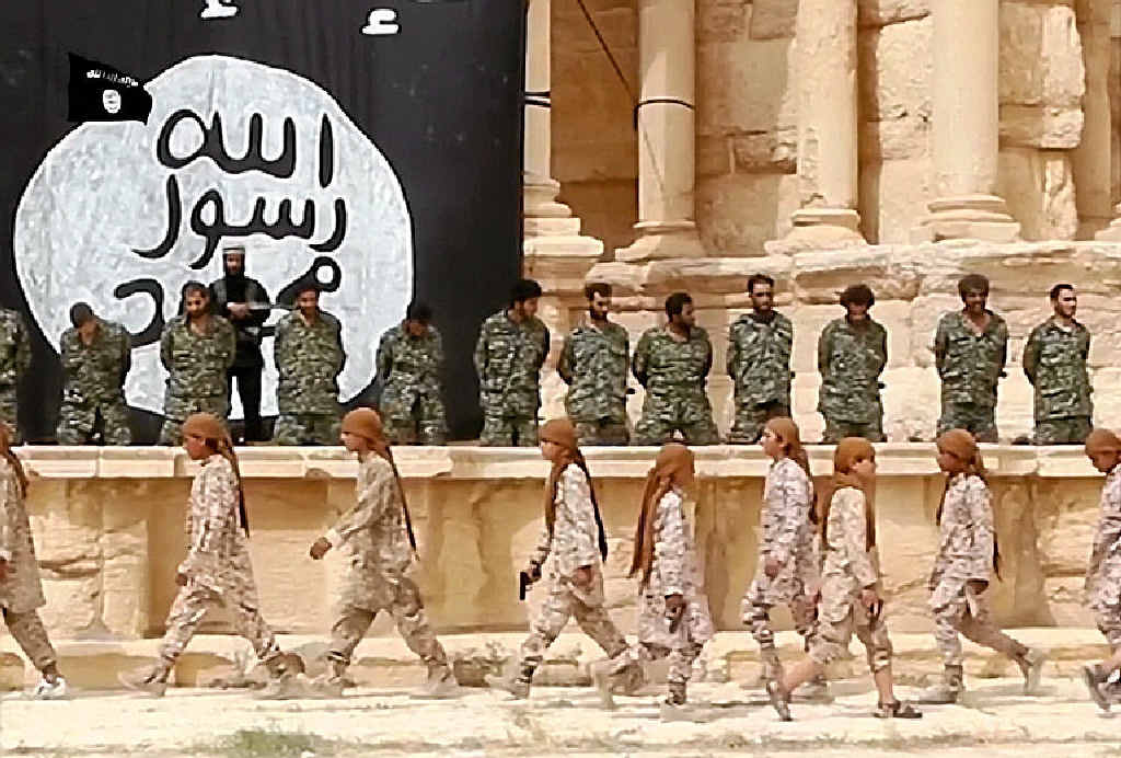 GRUESOME VIOLENCE: These grabs from an IS propaganda video allegedly show 25 Syrian government soldiers on their knees in the ancient amphitheatre in Palmyra awaiting their execution. It appears the soldiers were executed by children or teenagers.