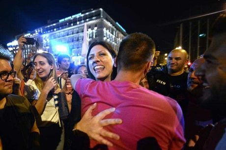 Greek parliament's president and Syriza party member, Zoe Kostantopoulou (C) embraces a 'NO' supporter , as she joins the celebrations in front of the parliament latein Athens on July 5, 2015. Greece's Prime Minister Alexis Tsipras said that the 'No' victory in the country's bailout referendum did not mean Athens was headed for a so-called Grexit.