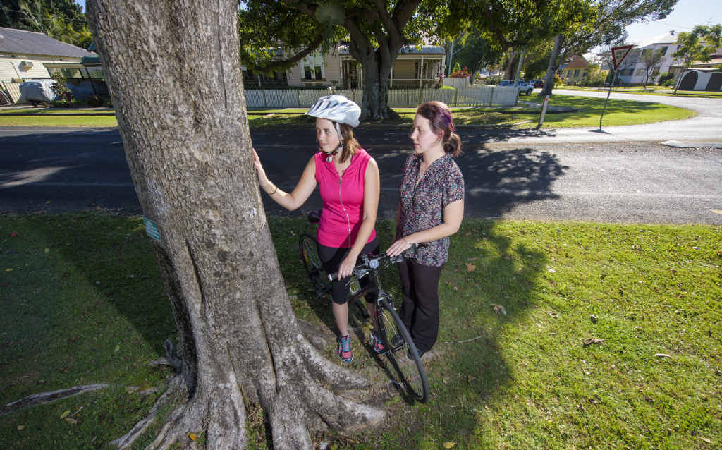 WRONG WIRING: Sophie Attwater and Emily Durrington look at the spot where they saw a piece of fishing wire strung across the road on Mary St between two trees. PHOTO: ADAM HOURIGAN