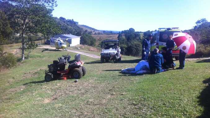 Paramedics and RACQ CareFlight helicopter medical staff help a woman who was injured in a ride-on lawn mower crash at a Federal property.