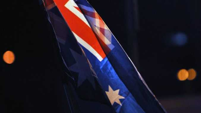 The Australian flag waved before the Anzac Day dawn service at Kings Beach, Caloundra.