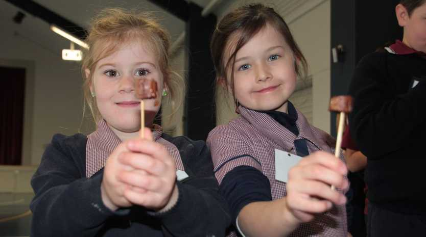 Quincy Austin (left) and Annabelle Arnold enjoy some kangaroo sausages at the Mary Mackillop Catholic College's NAIDOC Week celebrations. Photo Kate Dodd / The Chronicle
