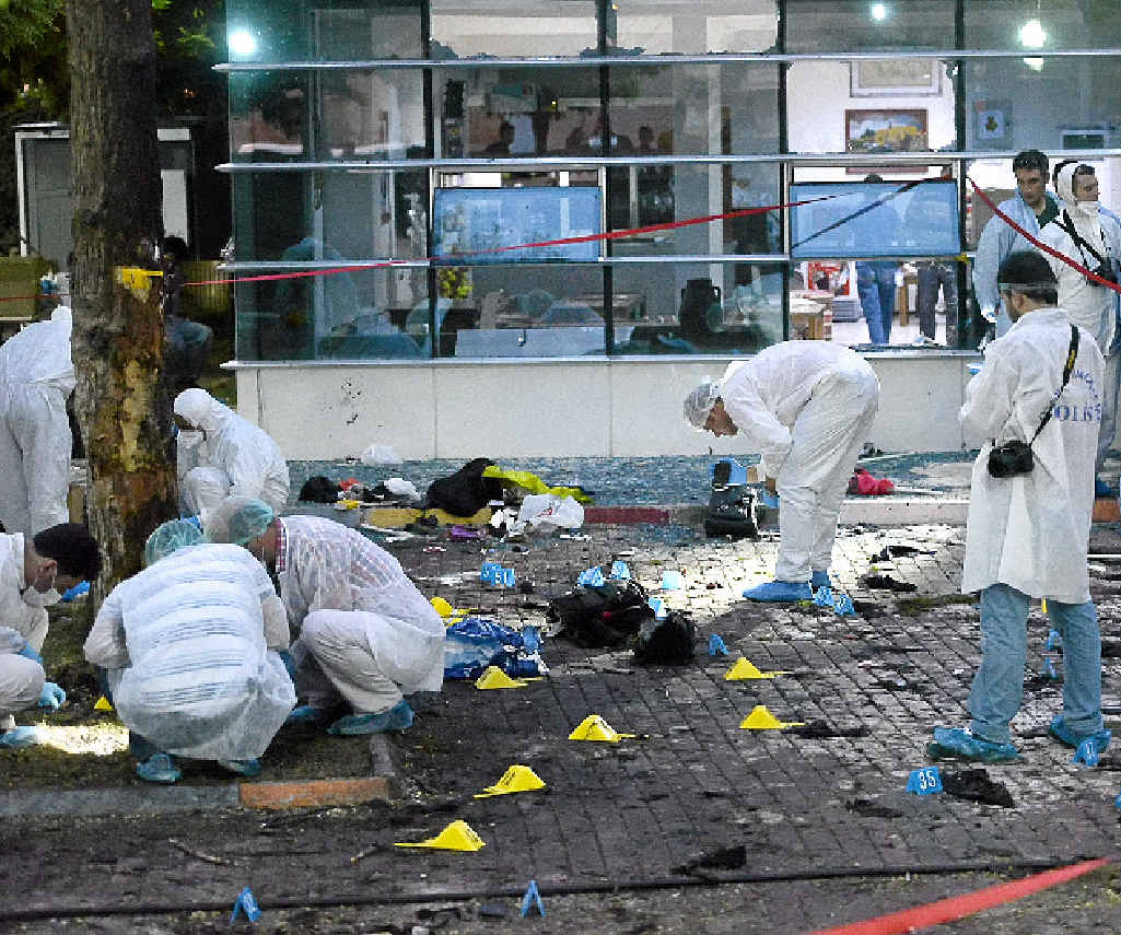 GRIM TASK: Turkish forensic police get down to business at the scene of the explosion in Suruc.